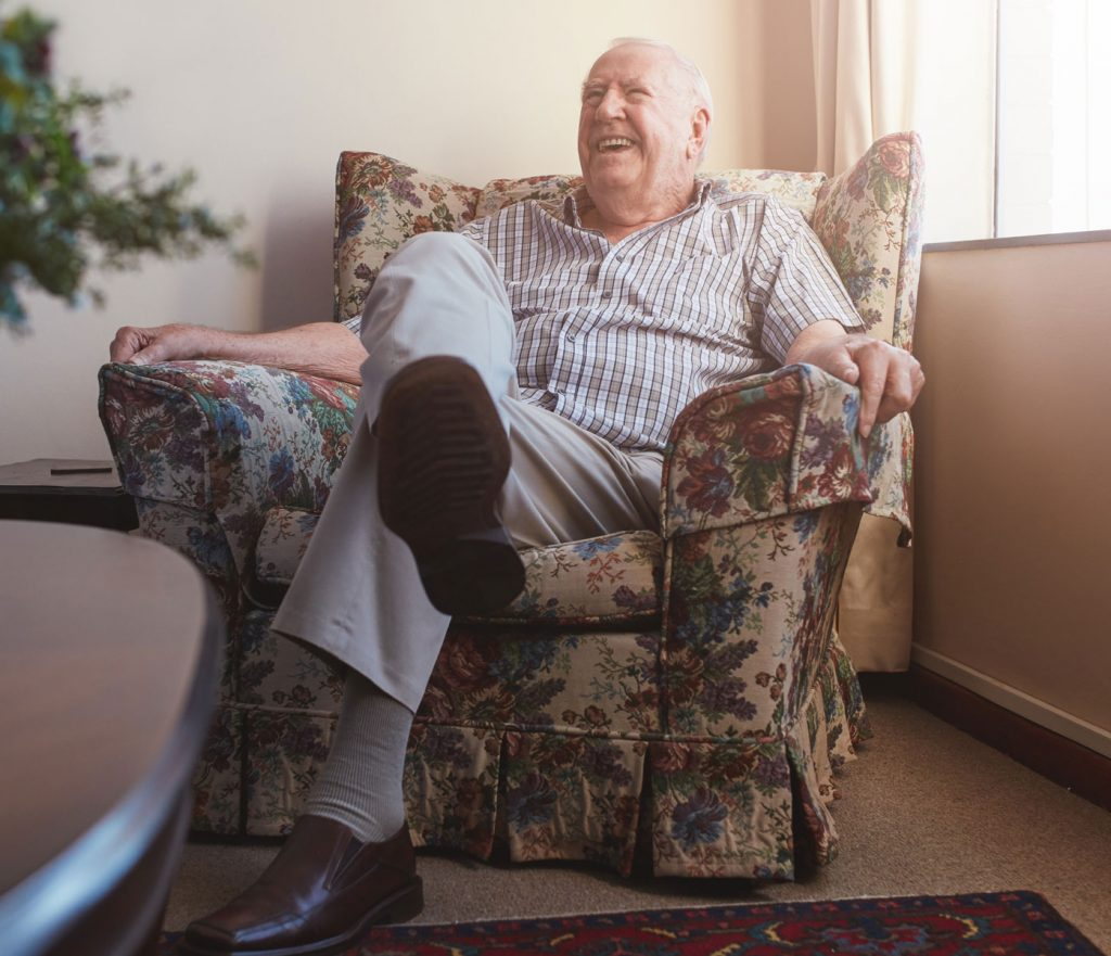 elderly man smiling in a chair